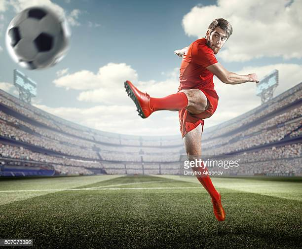 soccer player kicking ball in stadium - hitting stock pictures, royalty-free photos & images