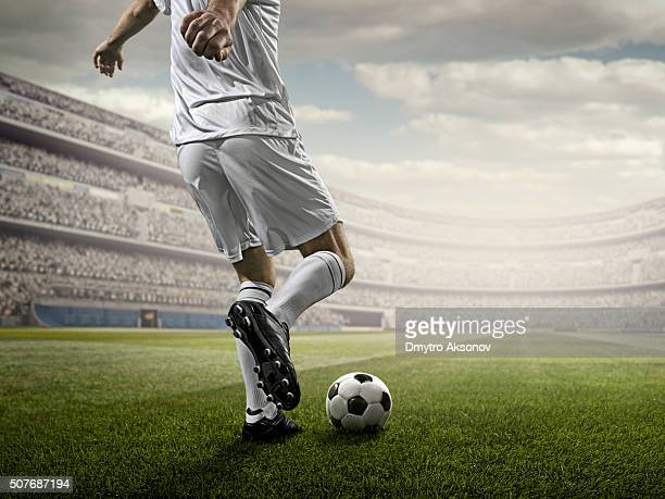 soccer player kicking ball in stadium - football league stock pictures, royalty-free photos & images