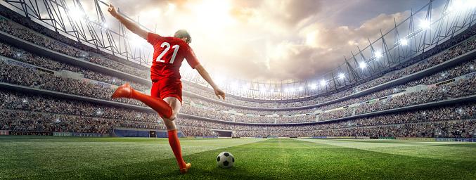 Soccer player kicking ball in stadium 507687506
