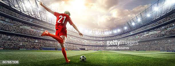 soccer player kicking ball in stadium - soccer stock pictures, royalty-free photos & images