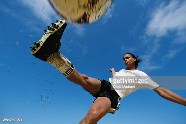Soccer player kicking ball, low angle view, close-up