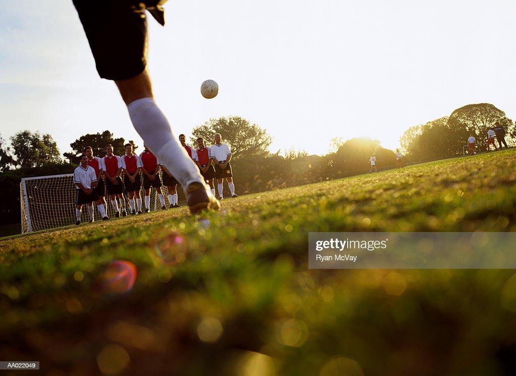 Soccer player kicking ball towards goal, ground view : Stock Photo