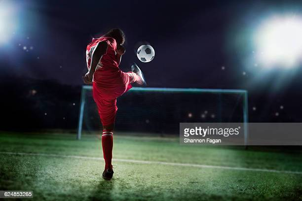 Soccer player kicking ball towards goal