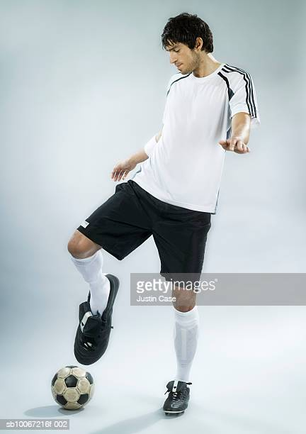 soccer player kicking ball with enlarged foot, studio shot (digital composite) - big foot stock photos and pictures