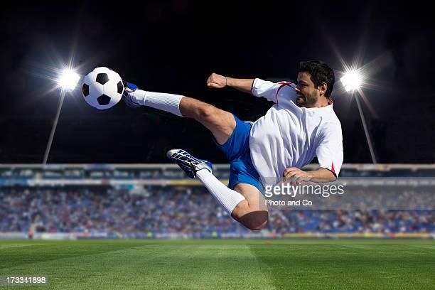 soccer player kicking in stadium