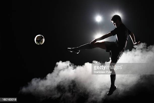 soccer player kicking the ball at night on stadium - fußballspieler stock-fotos und bilder