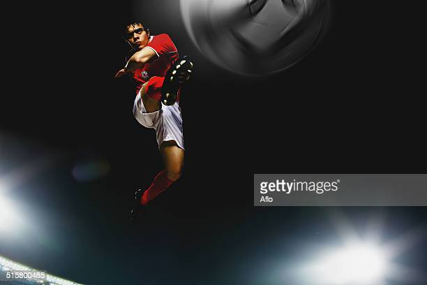 Soccer Player Kicking The Ball In Mid-Air
