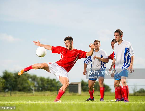 Soccer player kicking the ball on playing field.