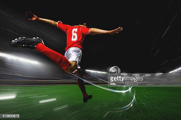 soccer player kicking the ball - softfocus stockfoto's en -beelden