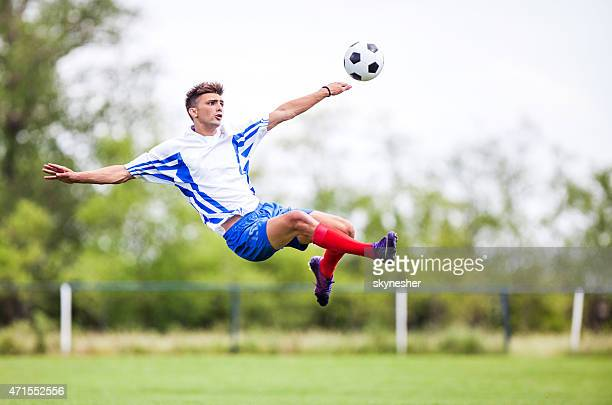 Soccer player kicking the ball while being in mid air.
