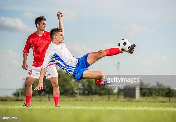 soccer player kicking the ball while being in mid air. - anfallsspelare fotboll bildbanksfoton och bilder
