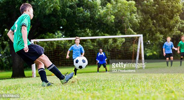 Soccer player kicks ball