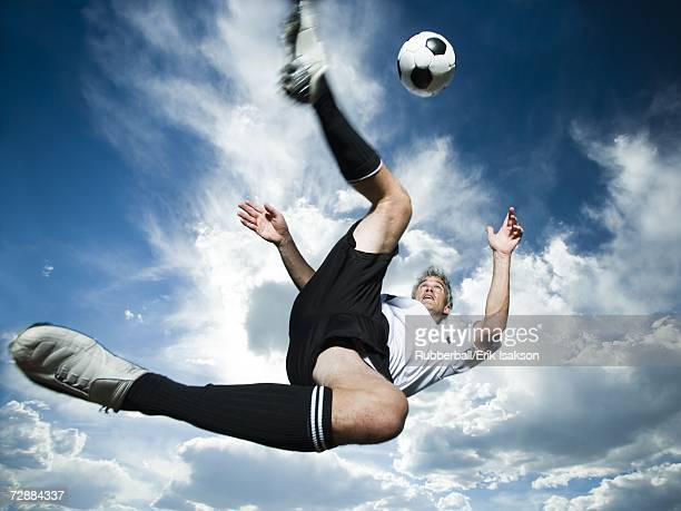 Soccer player kicks ball while silhouetted against a cloudy blue sky
