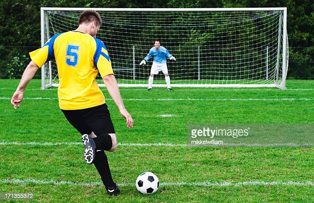 Soccer player kicks football - goalkeeper ready