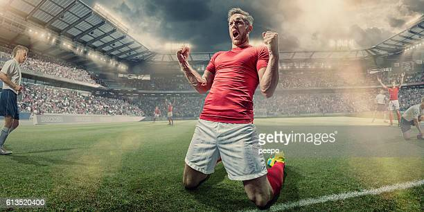 soccer player kneeling on pitch with clenched fists in celebration - fußballspieler stock-fotos und bilder