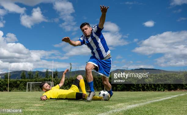 soccer player making a foul on the field - foul sports stock pictures, royalty-free photos & images