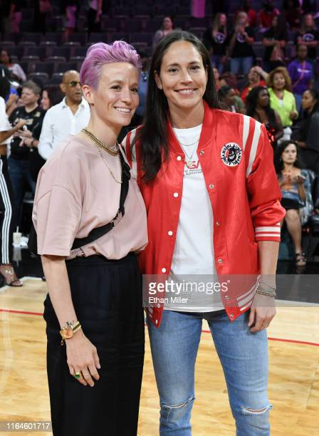 Soccer player Megan Rapinoe and Sue Bird of the Seattle Storm pose for photos on the court after attending the WNBA All-Star Game 2019 at the...