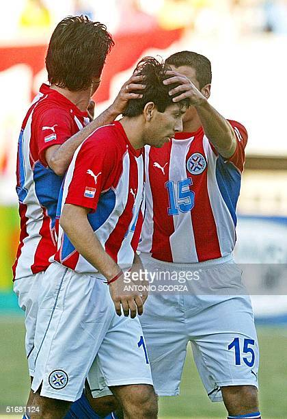Soccer player Nelson Cuevas is congratulated by Carlos Bonet and another unidentified teammate after scoring in Fortaleza Brazil 21 August 2002...