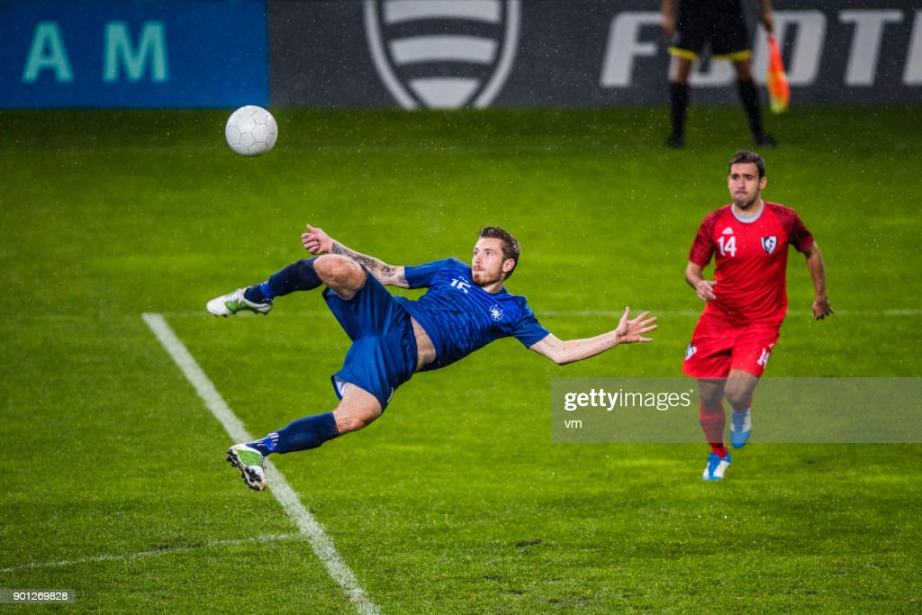 Soccer player performing a volley shot : Stock Photo