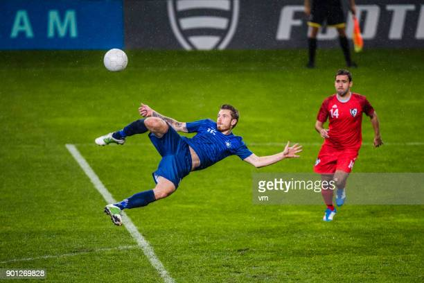 soccer player performing a volley shot - match sport stock pictures, royalty-free photos & images
