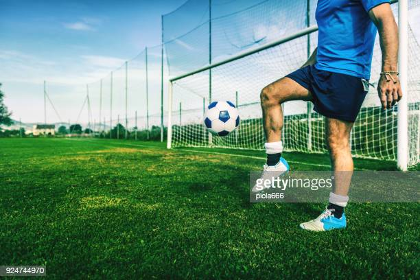 Soccer player playing with ball in a football field