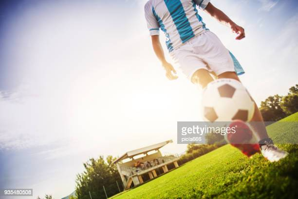 soccer player playing with ball in a football field - stunt stock photos and pictures