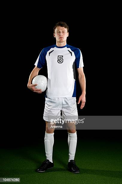a soccer player, portrait, studio shot - fußballtrikot stock-fotos und bilder