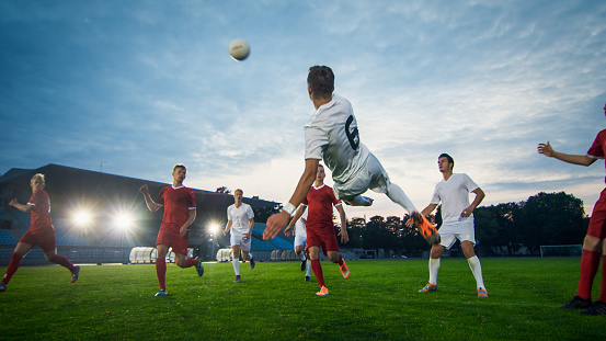 Soccer Player Receives Successful Pass and Kicks Ball to Score Amazing Goal doing Bicycle Kick. Shot Made on a Stadium Championship. 1161534865