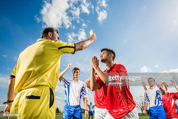 soccer player receiving a yellow card for making a foul. - yellow card stock pictures, royalty-free photos & images