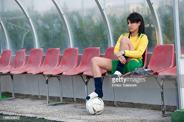 Soccer player relaxing in dugout