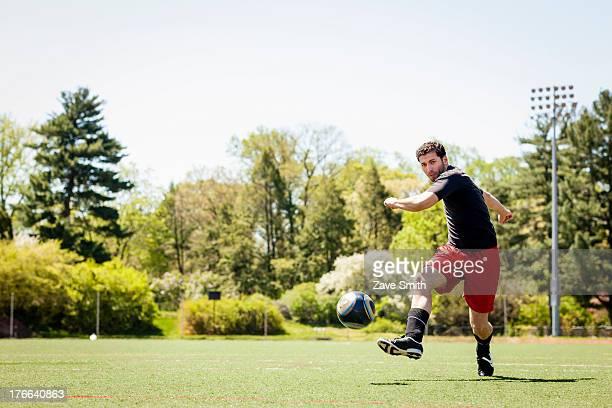Soccer player running and kicking ball
