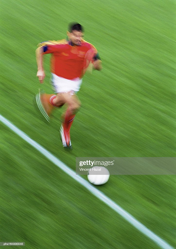 Soccer player running with ball, blurred. : Stockfoto