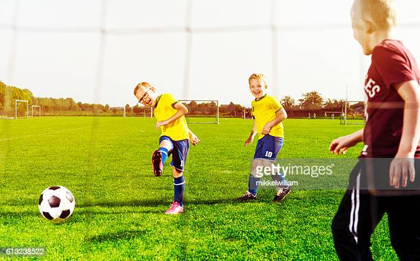 Soccer player shoots goal while playing with his football team