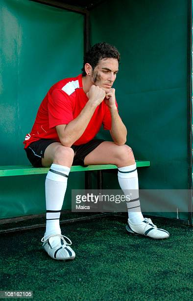 Soccer Player Sitting on Sidelines