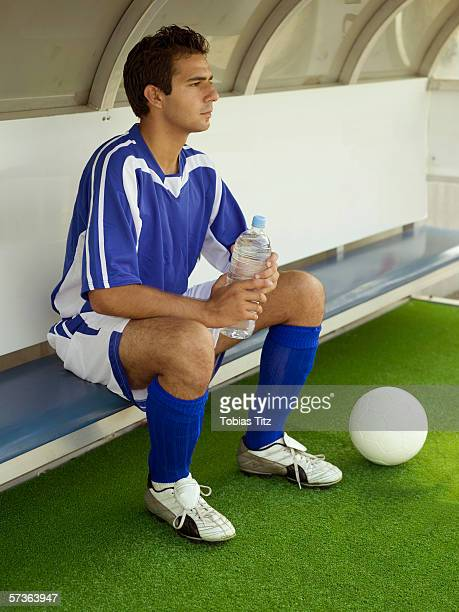 a soccer player sitting on the bench - スポーツユニフォーム ストックフォトと画像