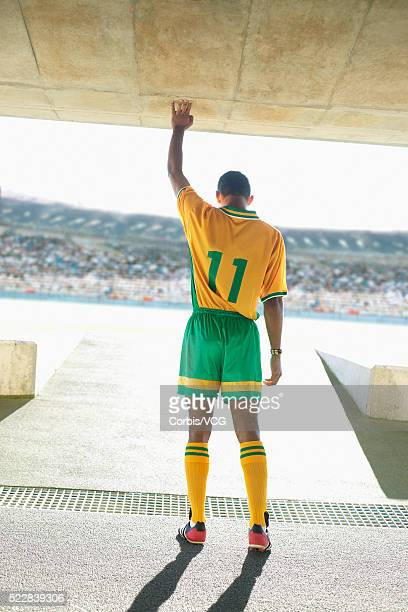 Soccer player standing in tunnel and looking out onto the field