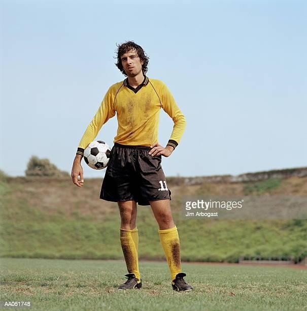soccer player standing with ball - jugador de fútbol fotografías e imágenes de stock