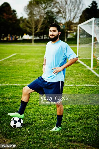 Soccer player standing with foot on ball