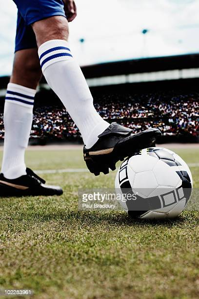 Soccer player stopping soccer ball with foot