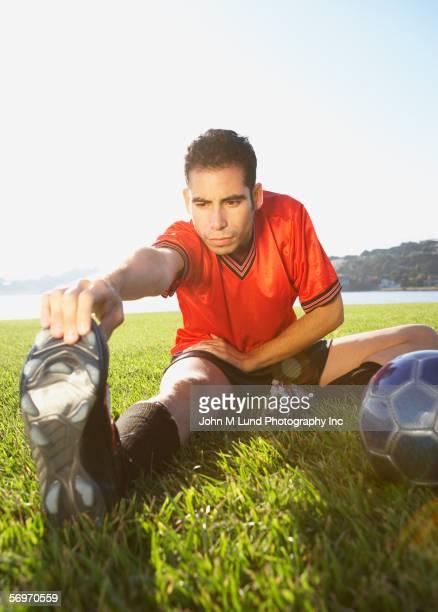 soccer player stretching in field - precalentamiento fotografías e imágenes de stock