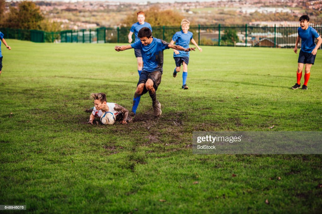 Soccer Player Tackled Down : Stock Photo
