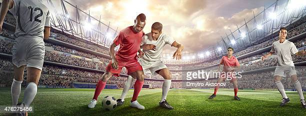 Soccer player tackling ball in stadium