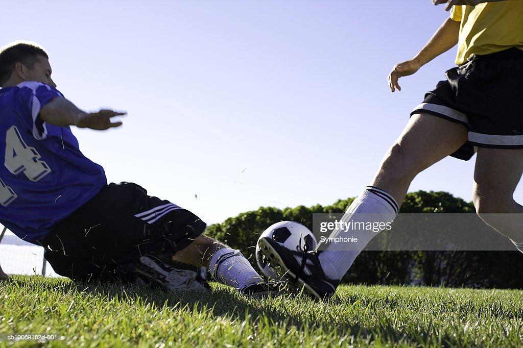 Soccer player tackling : Stockfoto