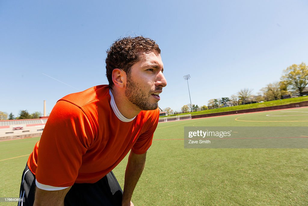 Soccer player taking a break on pitch : Stock Photo