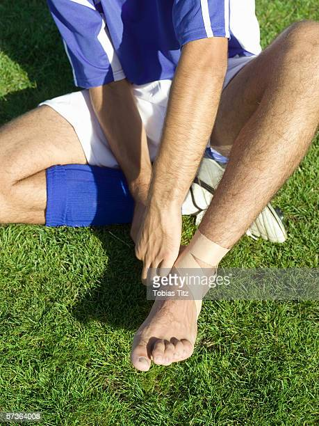 A soccer player taping up his ankle