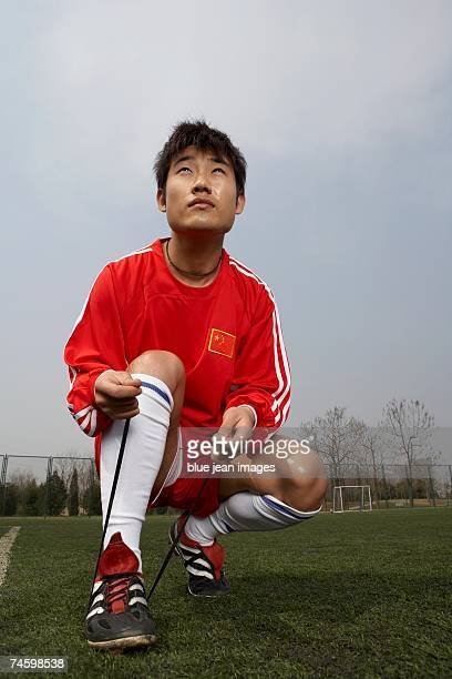 soccer player ties his shoe and prepares to return to the game - studded stock pictures, royalty-free photos & images
