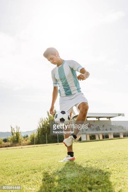 soccer player training on the field - bouncing ball stock photos and pictures