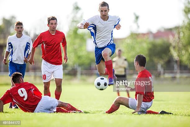 calciatore cerca di evitare i suoi oppositori durante la partita. - placcare foto e immagini stock