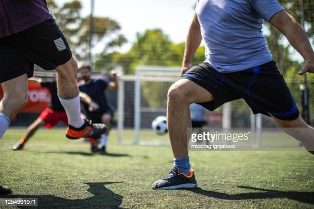fußballer versucht, ein tor während freundschaftsspiel zu schießen - angriffsspieler stock-fotos und bilder