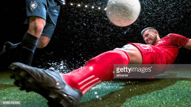 soccer player trying to slide tackle his opponent - tackling stock pictures, royalty-free photos & images